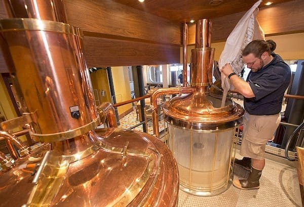 Carnival Vista Brewmaster Colin Presby pours malt into a mash tun located in the RedFrog Pub's brewery house. photo: Carnival